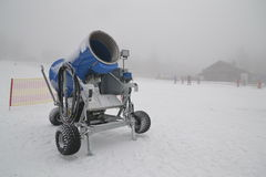 Snow cannon. Blue metal snow cannon in misty snowed in ski resort Stock Photography