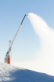 Snow cannon making artificial powder at the very top of a ski slope Royalty Free Stock Photo