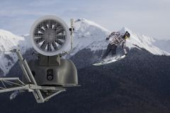 Snow cannon in the mountain ski resort and the flying snowboarder. Royalty Free Stock Image