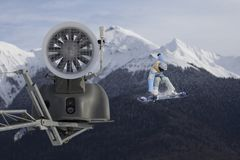 Snow cannon in the mountain ski resort and the flying snowboarder. Stock Photography