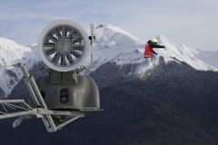 Snow cannon in the mountain ski resort and the flying snowboarder. Royalty Free Stock Photography