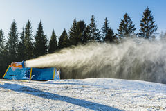 Snow cannon during the production of artificial snow. Stock Photography