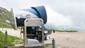 Snow cannon in a ski resort. in the Alps. Ski slope without snow during warm spring. Not season. royalty free stock photos