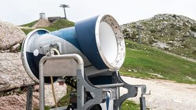 Snow cannon in a ski resort. in the Alps. Ski slope without snow during warm spring. Not season. royalty free stock images