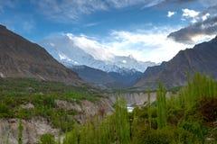 Snow cap mountain under blue sky and green Poplar forest along H. Unza river, Hunza Valley, Gilgit, Balistan, Pakistan Stock Photo