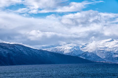 Snow caped mountain range. In Norway under a blue cloudy sky royalty free stock photography