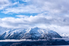 Snow caped mountain. Range under a blue cloudy sky royalty free stock photography