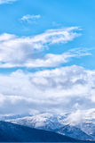 Snow caped mountain range. Under a blue cloudy sky. Vertical composition royalty free stock image