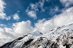 Snow caped Mountain. Under blue sky with white puffyes royalty free stock photos
