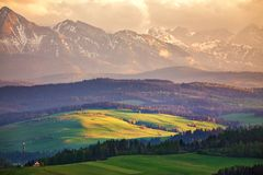 Snow caped mountains and green fields and meadows. In Malopolska region, Poland. Spring sunset in Tatra Mountains, Pieniny range royalty free stock photography