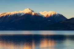 Snow-caped mountains and lake on sunset. Nature landscape. Lake Wakatipu, New Zealand stock photo