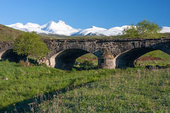 Snow-capped Aragats mountain and ancient bridge in green. Old bridge on green hill and Aragats mountain covered with snow Royalty Free Stock Photo