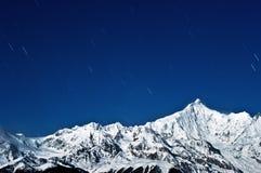 Snow-capped bergen de sterren Stock Afbeelding