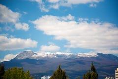 Snow-capped bergpieken en witte wolken stock afbeelding