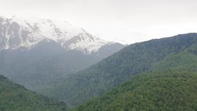 Snow-capped Caucasus mountains 005. Contrast of Caucasus mountains, green forests against snow-capped mountains stock video footage