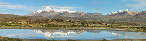 Snow capped high mountains reflected in Lake Chungara Royalty Free Stock Images