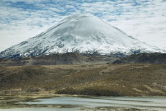 Snow capped high mountains reflected in Lake Chungara. Snow capped Parinacota volcano reflected in Lake Chungara, Lauca national park, northern Chile. The Stock Photo