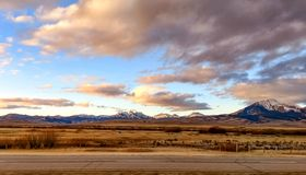 Snow capped Idaho mountains. A side of the road view of a beautiful Idaho morning with partly cloudy sky and snow covered mountains in the background stock photos