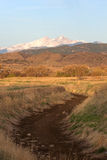 Snow Capped Longs Peak in Colorado. A Snow Capped Longs Peak in Colorado. The dry creek bed won't be empty for long when the snow melt from the mountains fill it stock photo