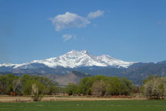 Snow capped Longs Peak and Mt Meeker on a spring or summer day. Beautiful view of the snow capped Longs Peak and Mt Meeker with spring green field and trees in Stock Images