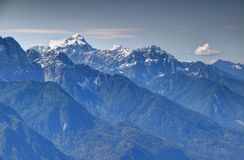 Snowy Mangart peak and forested ridges in Julian Alps, Slovenia Royalty Free Stock Photo
