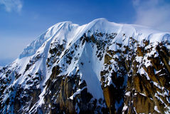 Snow Capped Mountain in Denali Park. Packed Snow Capped Craggy Sheer Mountain Peak.  Aerial View of the Great Alaskan Wilderness, Denali National Park, Alaska Royalty Free Stock Photos
