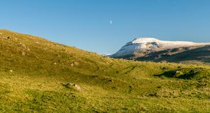 Snow capped mountain with the moon stock image