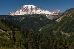 A snow capped mountain, Mount Rainier, at spring time with a forest of lush green pine trees in the foreground and road stock image