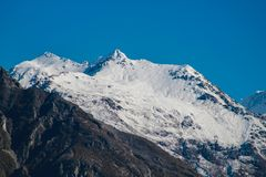 Snow capped mountain peak with clear blue sky stock photography