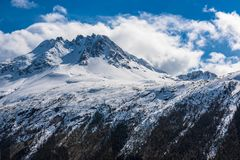 A Snow Capped Mountain Peak in Skagway Alaska. A snow capped mountain peak in the Skagway mountains with a blue sky background Stock Photography