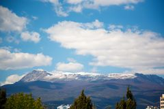 Snow-capped mountain peaks and white clouds stock image