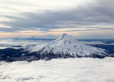 Snow-capped mountain peak from the air. Snow-capped mountain peaks of mt hood rise above the clouds in Oregon Royalty Free Stock Photo