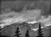 Snow capped mountain peaks with storm clouds Stock Images