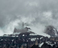 Snow capped mountain peaks with storm clouds Royalty Free Stock Image