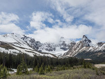 Snow capped mountain peaks with storm clouds Royalty Free Stock Photos