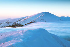 Snow-capped mountain peaks, among them a fluffy cloud, cold, fro. Panorama of snow-capped mountain peaks, among them a fluffy cloud, cold, frosty sunset Stock Images
