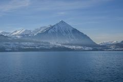 Snow-capped mountain seen from a cruise boat at Lake Thun, Switzerland, Europe. Winter 2017 Stock Photos