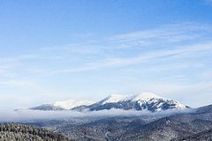 Snow capped mountain. Against the blue sky Royalty Free Stock Photos