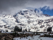 Snow capped mountain with trees in foreground Royalty Free Stock Images