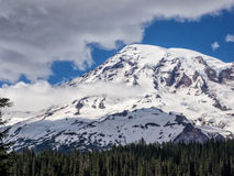 Snow capped mountain with trees in foreground Stock Photo
