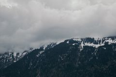 Snow-capped Mountain Under Cloudy Sky Stock Photo