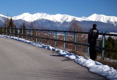 Snow-capped mountains. A female tourist looks at the distant snow-capped mountains stock photo