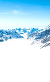 Snow-capped mountains against the blue sky Stock Images