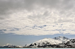 Snow Capped Mountains, Alaska. Snow covered mountains in Glacier Bay National Park under bold clouds and blue skies on the inside passage of coastal Alaska Royalty Free Stock Photo