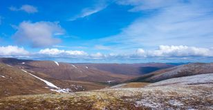 A springtime panoramic view of the rockies as seen from a high altitude. Snow-capped mountains as seen from a summit in the alaskan wilderness Royalty Free Stock Photos