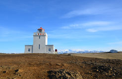Snow Capped Mountains Behind Dyrholaey Lighthouse in Vik. Beautiful snow capped mountains behind Dyrholaey Lighthouse in Iceland royalty free stock photography