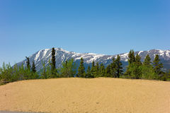 Snow-capped mountains behind sand dunes in alaska Stock Images