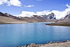 Snow capped mountains with blue lake. Snow capped mountains of Himalayan range along the blue lake called as Gurudongmar Lake at an altitude of 17,100 feet above Stock Photo
