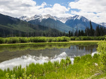 Snow capped mountains and clear lake Stock Photography
