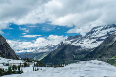 Snow-capped mountains in Glacier National Park. Puffy clouds frame the Rocky Mountain range as it winds through Glacier National Park Stock Photography